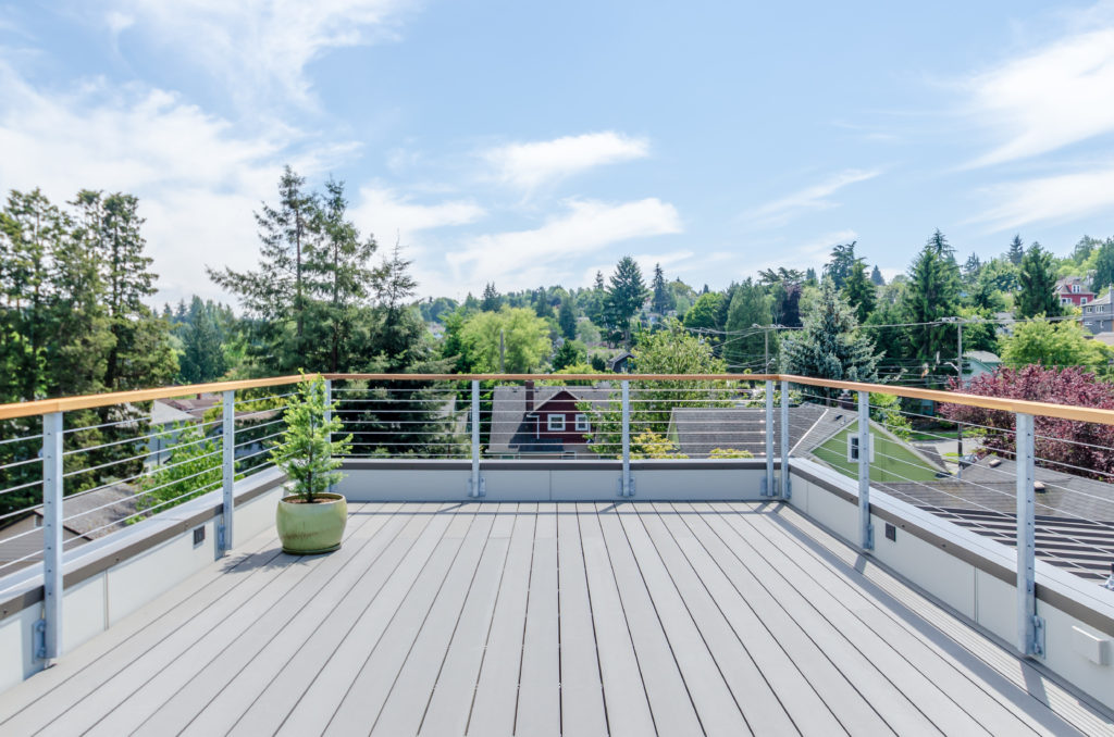 A modern deck overlooks a luscious green Seattle neighborhood
