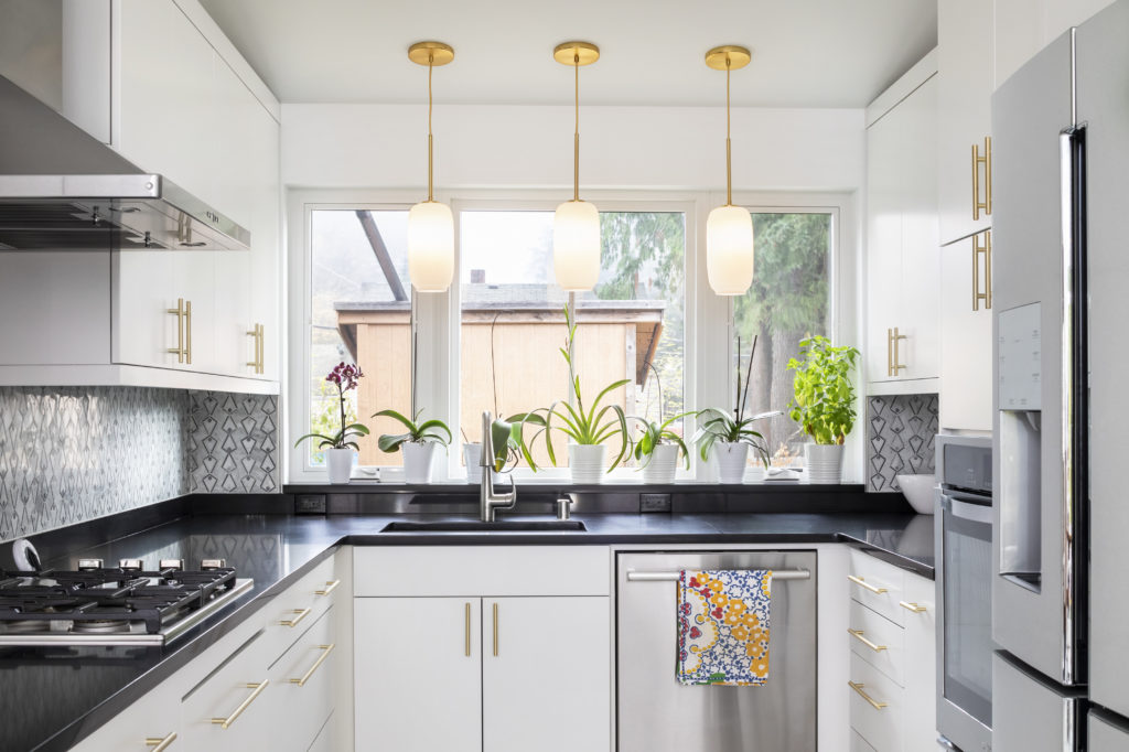 A modern sustainable kitchen with white and gold cabinetry, black counter tops, natural light, and greenery